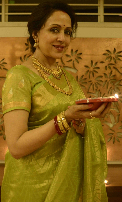 Hema Malini holds up a diya as she poses in front of the camera after a grueling 18-hour day