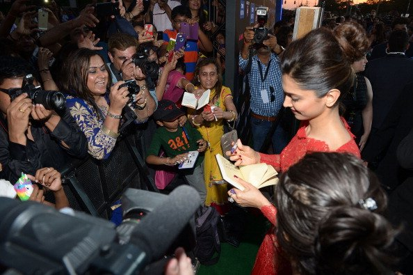 Fans and mediapeople congregate around Deepika Padukone when she arrives for a media interaction in this undated picture.