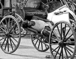 A rickshaw puller takes a quick nap. Photo by Sirsendu Gayen in Kolkata.