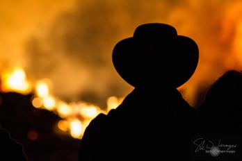 Silhouette of a man in a hat, against a backdrop of roaring flames from a communal bonfire, part of the annual tradition known as Fireworks Night, Bonfire Night or Guy Fawkes Night, across the UK. For the week around November 5th, bonfires are lit and fireworks released to commemorate the foiling of the 1605 Gunpowder Plot, against the Parliament of King James I.
